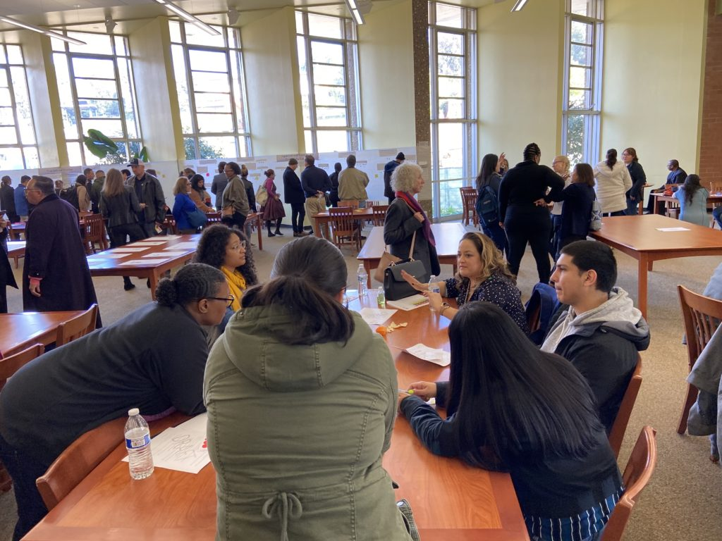 People at all college day, talking in groups and pairs in library.  Back of room has white paper with activity