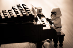 A storm trooper lego toy playing a lego piano